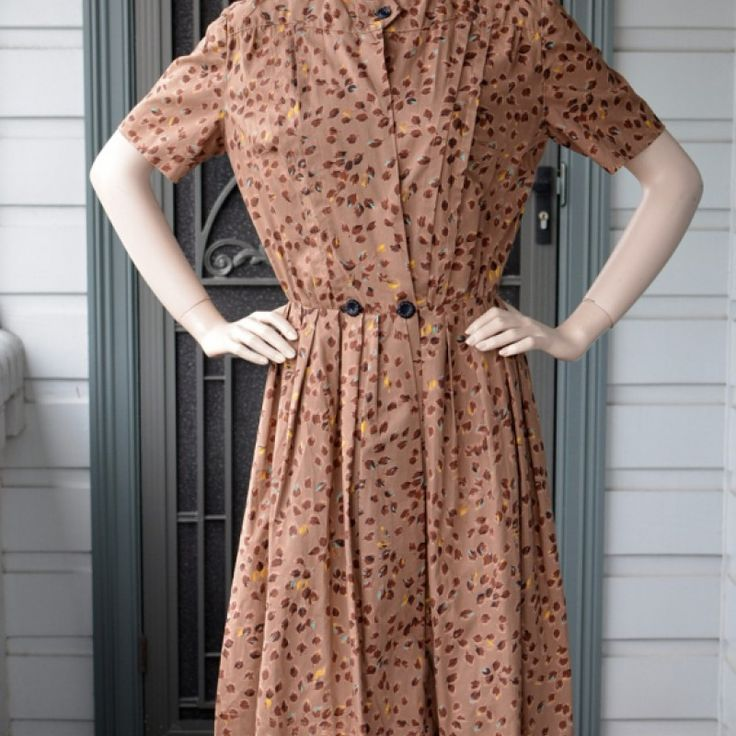 1950s Taupe Fit and Flare Dress on Velvet Rose's Pin Up Dressing Room  Original 50s cotton home sewn dress Lovely brushstroke leaves pattern in Autumn tones. Fitted bodice with sewn in pleats to the front. Button at the neck and 2 at the waist, concealed press studs in between. The press studs look to be a later addition. Short sleeves. Pleated full skirt around knee length or just below. Home sewn good job. The button holes which are covered by the buttons have the home made look only…