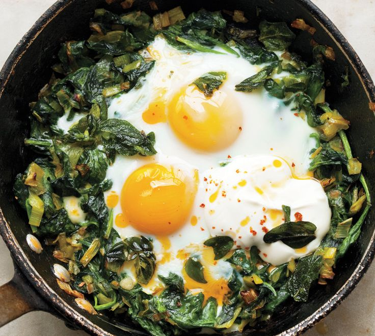 Yotam Ottolenghi's skillet baked eggs: spinach with melted leeks and scallions, baking eggs on top, and finishing with a dollop of yogurt and a drizzle of butter spiced with a smoky Turkish chili powder known as kirmizi biber (though crushed red pepper flakes will also work).