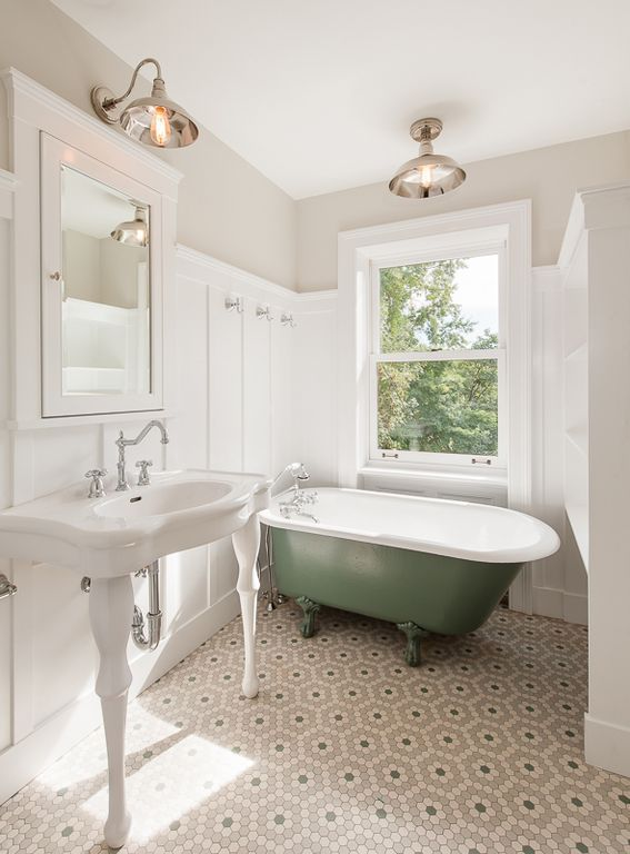 traditional full bathroom with wainscoting builtin bookshelf penny tile floors flush