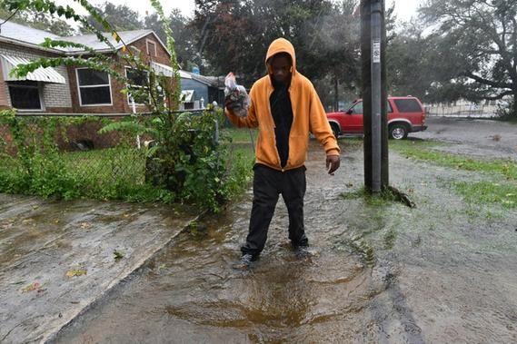 Un habitant de Jacksonville marche dans une rue inondée, après le passage de l'ouragan Matthew, le 7 octobre 2016 en Floride - Un habitant de Jacksonville marche dans une rue inondée, après le passage de l'ouragan Matthew, le 7 octobre 2016 en Floride - AFP JEWEL SAMAD