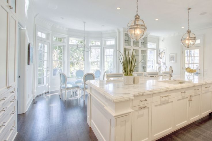 A pair of Restoration Hardware Victoria Hotel Pendants illuminate a long kitchen island topped with white marble framing square sink and polished nickel faucet lined with white and blue counter stools.