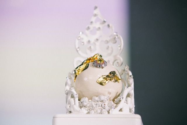 White Perle filled with a mousse of dates, spices and liquid gold, placed on a bed of silver-encrusted pistachio sponge and placed within a white meringue tiara. - by Vincent Gadan