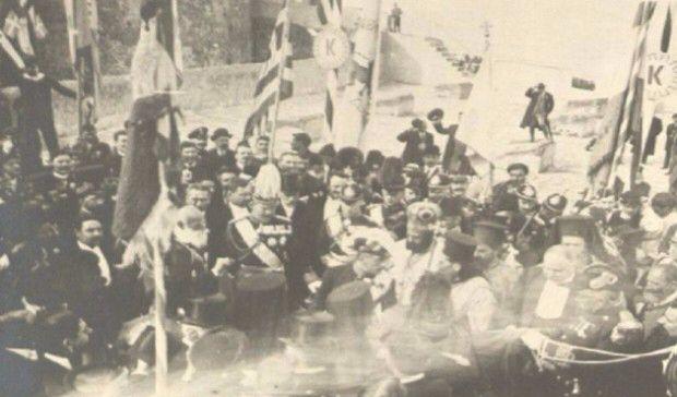 Κυριακή 1η Δεκεμβρίου 1913 *...είναι ακριβώς η στιγμή που ο βασιλέας Κωνσταντίνος  και ο πρωθυπουργός Ελευθέριος Βενιζέλος ετοιμάζονται να παραδώσουν  τη σημαία στους γηραιούς αγωνιστές Αναγνώστη Μάντακα και  Χατζημιχάλη Γιάνναρη προκειμένου να την υψώσουν στον πιο ψηλό ιστό.  Στο μέσο περίπου της φωτογραφίας και λίγο προς τα αριστερά διακρίνουμε  τον μονάρχη Κωνσταντίνο και αριστερά του, με το ημίψηλο καπέλο,  τον Ελευθέριο Βενιζέλο, ντυμένο επίσημα, όπως απαιτούσε η στιγμή.  Στα δεξιά του…