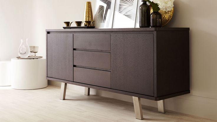 Pair a dark wood sideboard, such as the Assi Wenge Dark Wood Sideboard from Danetti, alongside some high gloss side tables for a contrasting yet sleek setting.