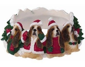 "Christmas Basset Hound Candle Ring by Basset Hound. $9.95. A fun and unique gift for lovers of this breed, our candle ring features a circle of furry merrymakers dressed in their holiday best and surrounded by snow and evergreens. This candle ring is sculpted in resin and handpainted, and fits  a 3"" candle (not included). Candle ring  measures 4.5"" wide and 2"" high."