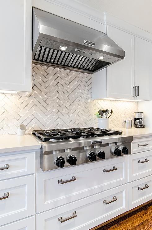 chic white kitchen features white shaker cabinets paired with white quartz countertops and a white herringbone herringbone