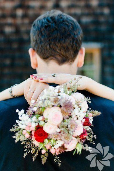 Gelin çiçeğinin ön plana çıkarıldığı bir düğün fotoğrafı.