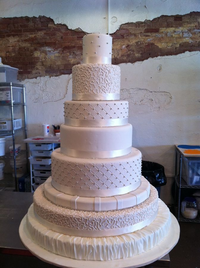 its a 7 tier wedding cake covered in an ivery fondant.  Ribbon and rhinestones are placed at the base of each tier