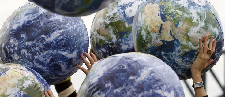 People hold up inflatable world globes during World Environment Day celebrations in central Sydney June 5, 2009.  REUTERS/Daniel Munoz