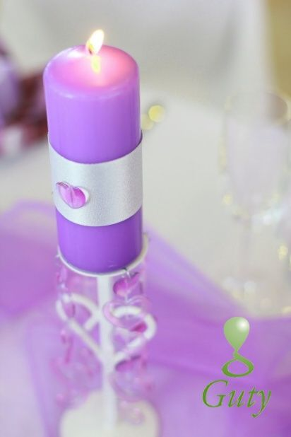 Fialová sviečka na svadbu na kovovom srdcovom svietniku.