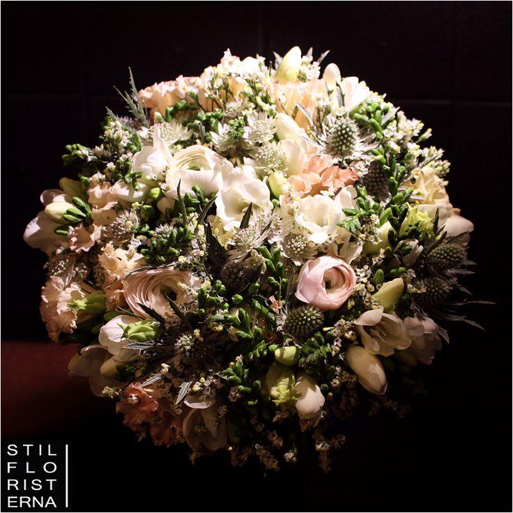 Magiskt vacker brudbukett med vårkänsla i ljusa romantiska toner, handbunden i något större rund form med bland annat ranunkel och tistlar.