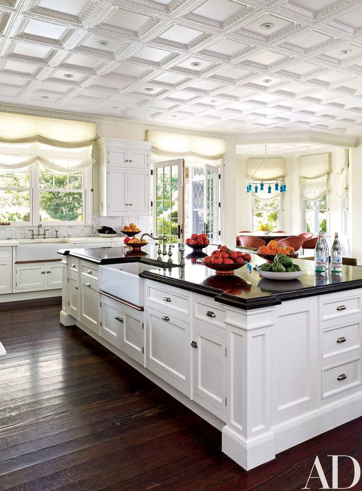 The kitchen, painted in a Farrow & Ball white, features Roman shades in an Old World Weavers fabric.