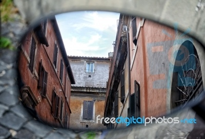 Old Italian Architecture Reflected In A Motorcycle Mirror. Stock photo.