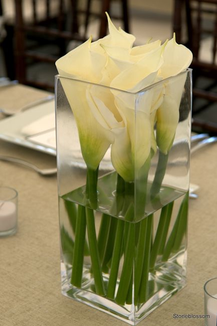Simple Calla in glass vase....add some gemstones at the bottom and it will glow with our chandelier lighting. ~ Pi Banquet Hall