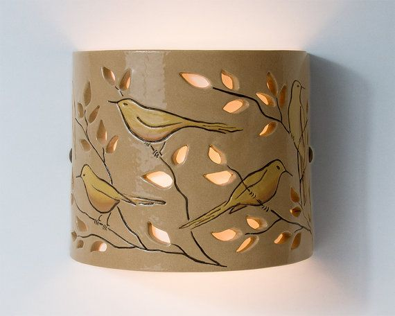 This wall light is hand made of stoneware. The design of the birds on the branches is hand painted and the cutting design of the leaves becomes part of the drawing. The leaf-holes allow the light to penetrate and thus create a lovely effect when the light is on. The reflection of the light shines upwards and downwards. This unique wall light with its soft colors creates a warm and pleasant atmosphere. It can decorate your living room or any other room in your home.  This is a finished…