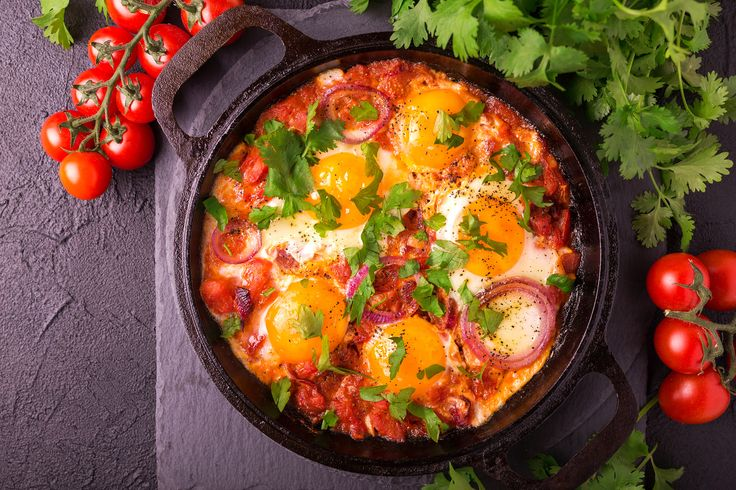 Shakshuka in iron pan with ingridients. Traditional Israeli cuisine. Fried eggs with vegetables. Top view. Middle eastern breakfast or lunch