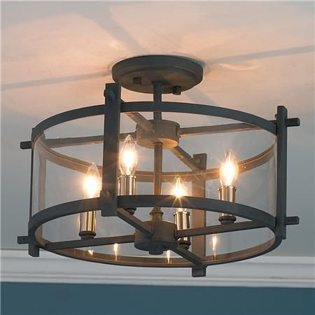 "Clearly Modern Semi-Flush Ceiling Light     Clear curved glass is enclosed in dark charcoal gray iron strapping for a mix of modern and industrial for a super interesting ceiling light that will please your designer palette.   4x60 watts. (candle base socket)   (11""Hx16.75""W)   5"" canopy Product SKU:FM11017 IR  Price:  $269.00"