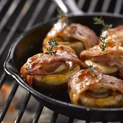 Wrap each mushroom in a slice of bacon and secure with a toothpick. Dip in barbeque sauce and place on braai. Keep turning until bacon is crisp. Serve.