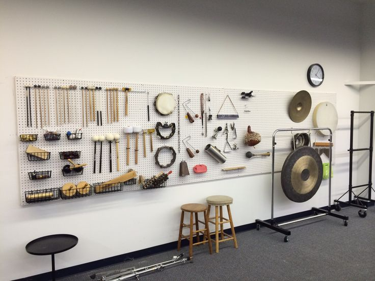 Pegboard as storage solution for auxiliary percussion equipment.