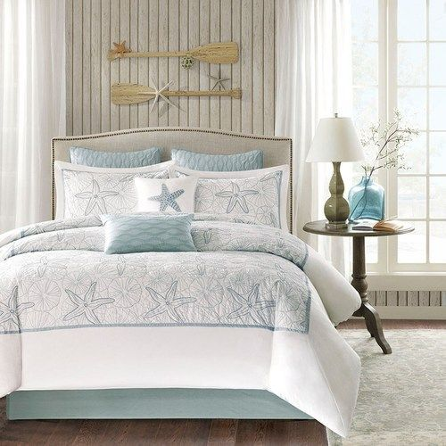 a soft seafoam blue is the accent color used in this beach themed king size - Beach Themed Bedrooms