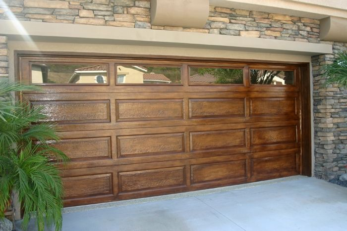 Faux wood garage door.  I just did our garage door this spring.  Only $40 for a quart of mustard-yellow paint and 2 quarts gel stain (2 different colors) .  Sealed with polyurethane so it would gradually patina/golden over time.  Looks amazing!!  Beats a couple thousand for a real wood door.