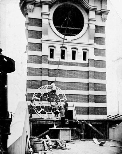 Workmen haul one of the clock's four dials into position atop the tower of Flinders Street station, Melbourne in 1909.