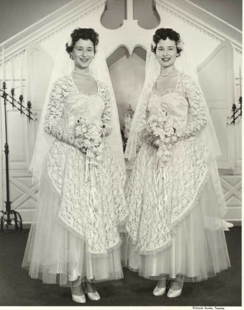 Description: The twin daughters of Mr. and Mrs. C.A. Green, Marlene and Darlene Green, were married in a joint wedding ceremony at the Little Church on the Prairie on August 11, 1954, their birthday. The two brides posed side-by-side in identical wedding gowns in front of the church altar. They appear to be carrying stephanotis bouquets and they have matching pearl necklaces. Marlene Green married Claude Flansburg while Darlene wed William Melville.