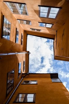 Photograph from an inner garden in Gamla stan, Stockholm, straight up in the sky. Orange houses reaching upwards. Available as poster at printler.com, the marketplace for photo art. Photographer Kevin Cho