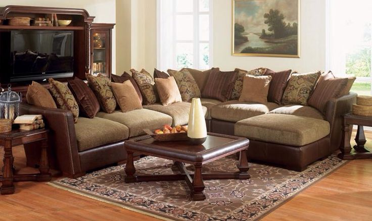 beautiful sectional sofa mixes Spanish Mediterranean and California mission style, for a cool blend of styles. The smooth track arms are dark brown, with classic nail head trim. Contrasting mossy green cushions and neutral throw pillows add even more flare. Plush back cushions and deep box seat cushions will keep you comfortable as you lounge on this sectional.