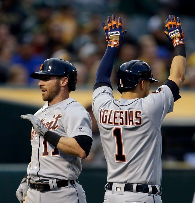Detroit Tigers' Andrew Romine, left, and Jose Iglesias (1) celebrate after scoring against the Oakland Athletics in the third inning. Both scored on an RBI-double by Tigers' Victor Martinez.