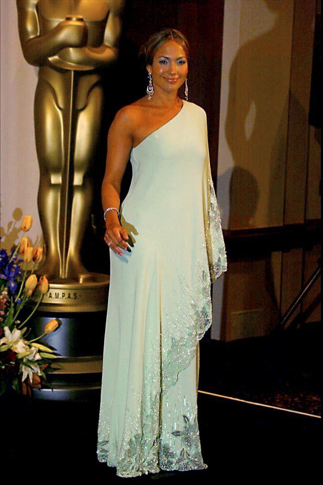 Jennifer López estaba guapísima, en los Oscar 2003, con un vintage de Valentino, una túnica en crepe de seda bordada y con el hombro al aire, que el modista había diseñado en los años 60 para la primera dama Jackie Kennedy. Este vestido pertenece a los archivos de la firma. El moño bajo y las joyas complementaron perfectamente el look.