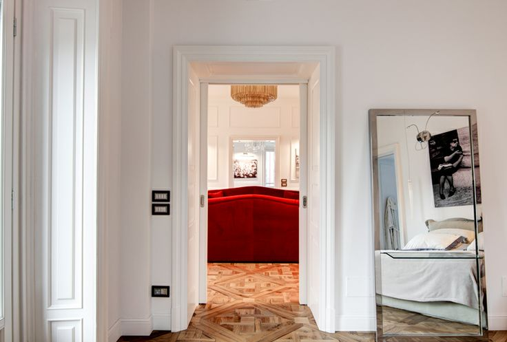 A classy chic apartment in central Milan by Nomade Architettura http://www.nomadearchitettura.com/#all  red velvet custom made sofas, timber floor, black and white pictures, photos, tv mirror, white custom made book case, venician murano chandelier, custom made iron mirror