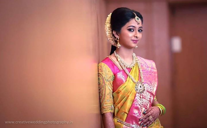 South Indian bride. Temple jewelry. Jhumkis.Yellow and pink silk kanchipuram…