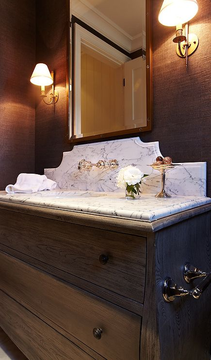 Brown powder room features walls clad in chocolate brown grasscloth wallpaper lined with a stained oak washstand topped with gray and white marble as well as a curved marble backsplash lined with a vintage style faucet under a rivet mirror illuminated by antique brass sconces