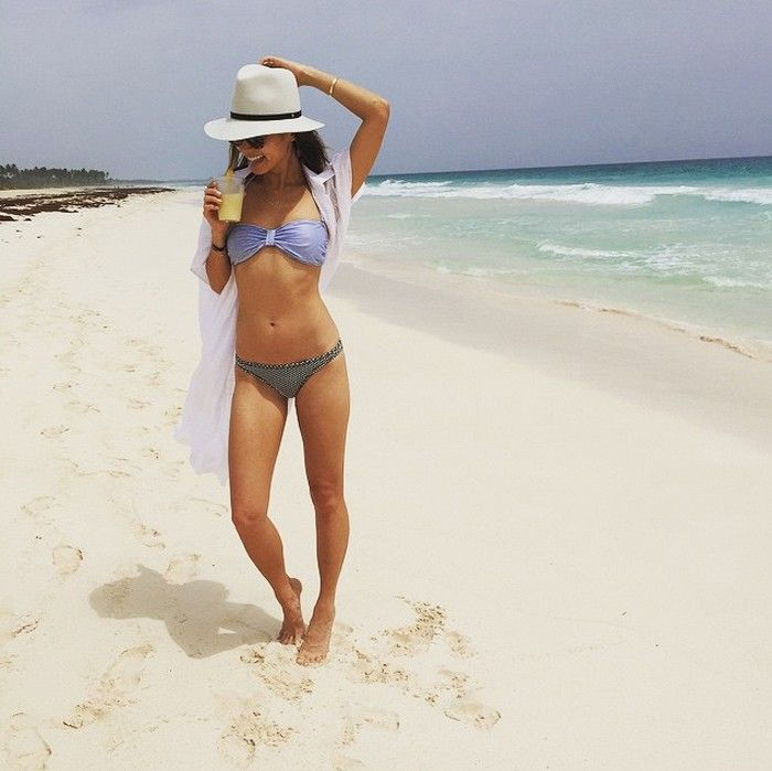 Jamie Chung wears a lilac bikini top with patterned bottoms, a white cover up and a hat.