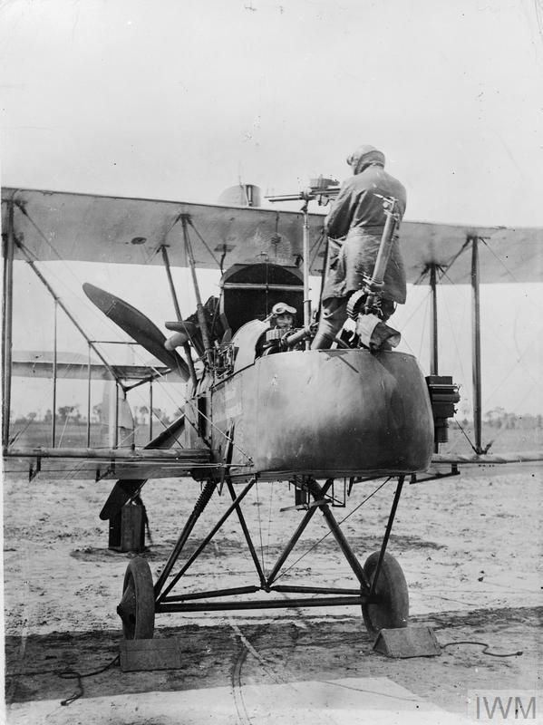 Lieutenant W C Cambray demonstrates the precarious stance required to use the rear-facing Lewis gun fitted to Royal Aircraft Factory F.E.2d biplane of No. 20 Squadron, Royal Flying Corps at Sainte-Marie-Cappel, France. Crew: pilot Captain Stevens, observer Lieutenant W. C. Cambray. The aircraft has a message displayed on the fuselage reading: 'Presented by the Colony of Mauritius No. 13'