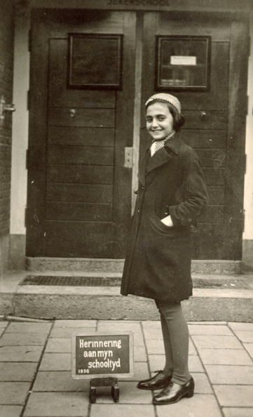 Margot Frank, standing in front of the doorway of the Jeker school in Amsterdam with a plaque at her feet that says 'memory of my school year 1936' in Dutch.