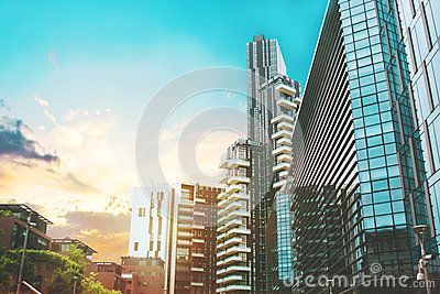 Beautiful multi colored toned aeroview image of Milan, Italian urban cityscape with skyscrapers and different buildings on the streets and background with the sunset