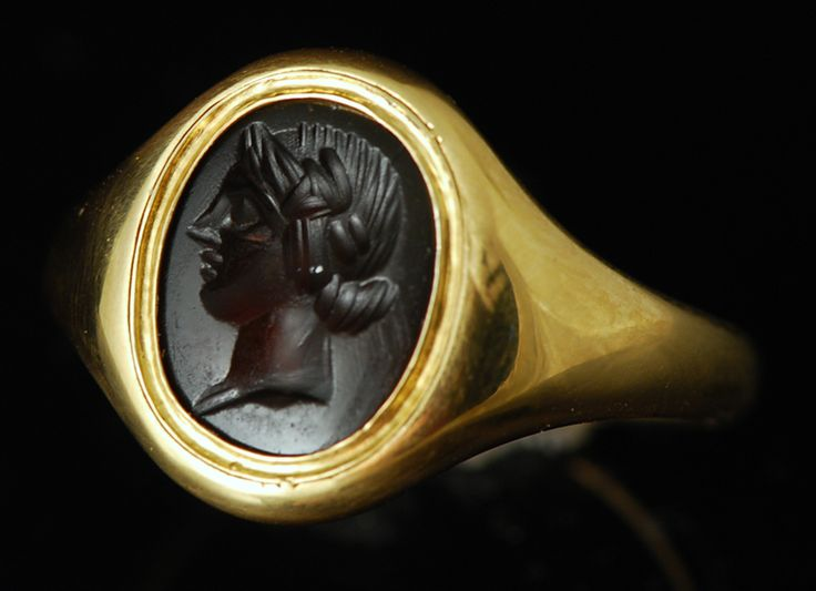 Intaille romaine en sardoine, de surface plate, prondément gravée d'un très joli buste d'éphèbe, probablement Adonis, d'une grande délicatesse de modelé. Beau portrait traité dans une belle matière.Excellent état. Monture en or 18k moderne, à fond clos, dans le style antique. Intaille d'époque romaine, du 1er siècle après notre ère.