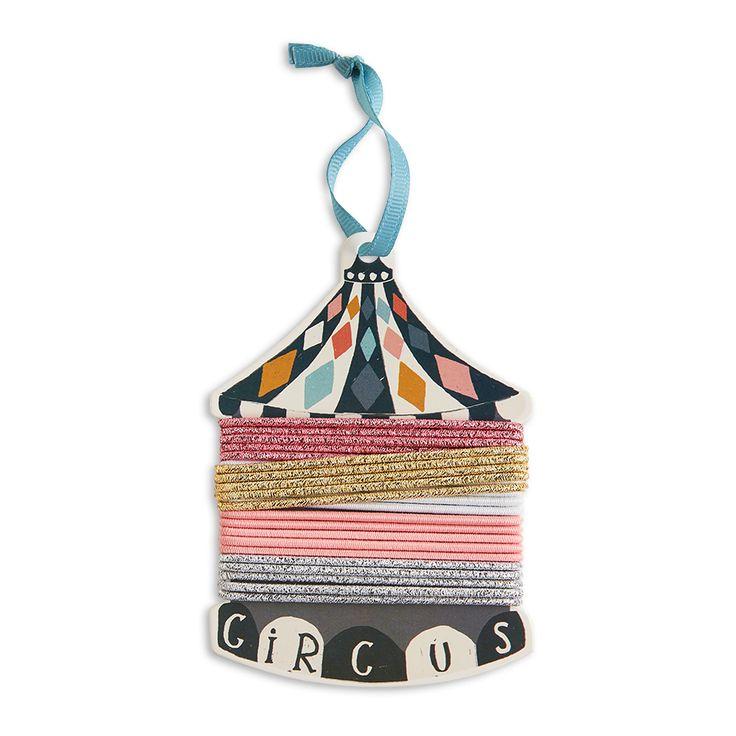 Färgglada och glittrande hårsnoddar runt en cirkusdekoration med en liten hängare i toppen.
