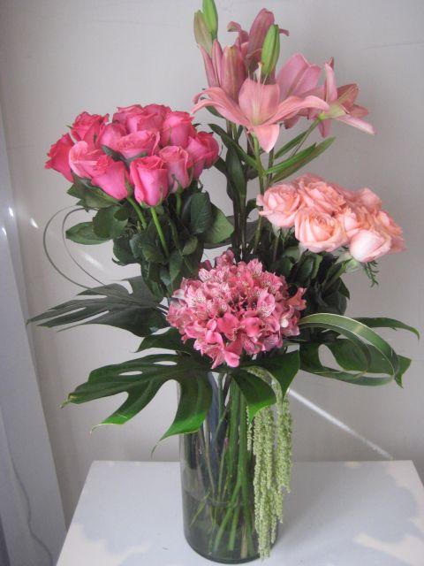 Cilindro con 24 rosas rosas, lilis rosas y astromerias rosas. Diseñado con dos bouquets de...