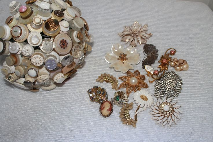 The making of a vintage button and brooch bouquet. All of the buttons and brooches were supplied by the bride. Some were pieces given to her and some were finds at local antique stores. Let http://couturekeepsakes.com/ make your one of a kind bridal keepsake.