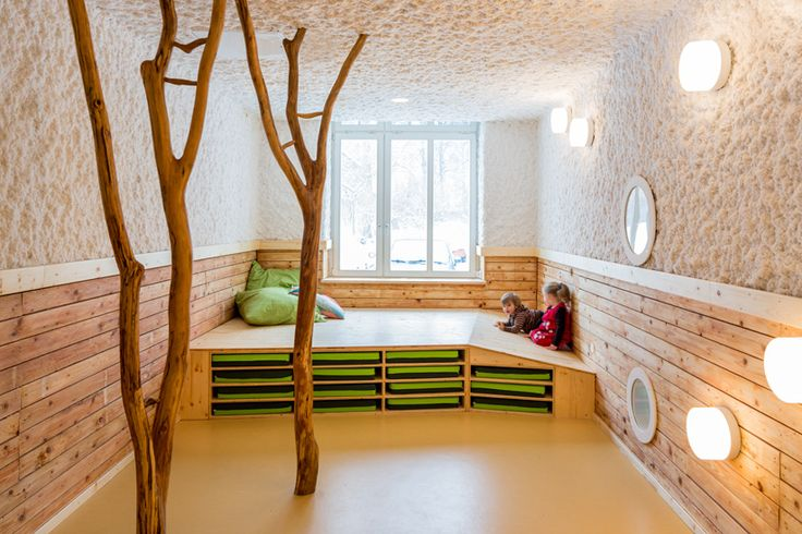 Baukind- Kita Drachenhöhle - The playrooms are left open and clutter free thanks to multifunctional objects and furniture: a raised platform for playing offers storage underneath, a wooden tunnel doubles as a bench and a hallway acts as a musical instrument. Trees installed throughout the playrooms encourage climbing and exercise in a whimsical way, while branch-like coat hooks adorn the walls. Subtle colour schemes, tiling and paintings continue the flow of references to nature and…