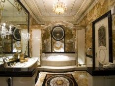 Extra Luxurious Bathroom In Gold Domination With Oval White Bathtub