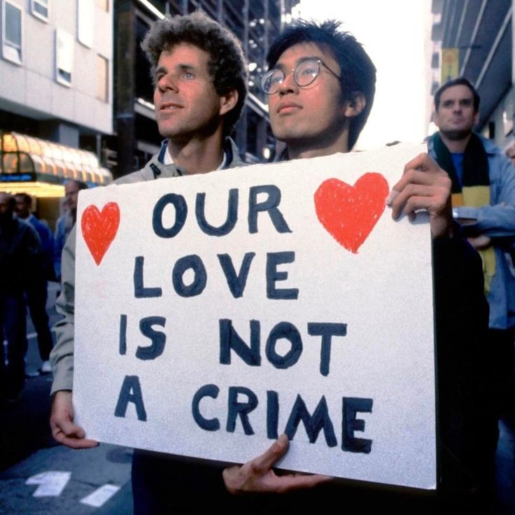 """OUR LOVE IS NOT A CRIME,"" demonstrators protest the United States Supreme Court's decision in Bowers v. Hardwick (1986), which upheld as constitutional state laws criminalizing sodomy, c. July 1986. Photo by Chuck Nacke, © Alamy. #lgbthistory #HavePrideInHistory"