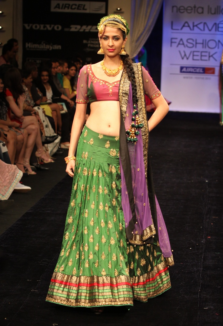 Green brocade lehenga with a pink blouse and purple dupatta.