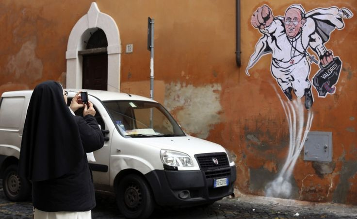 Super Francesco. Una suora scatta una foto al graffito di Papa Francesco su un muro vicino al Vaticano (Reuters/Alessandro Bianchi)
