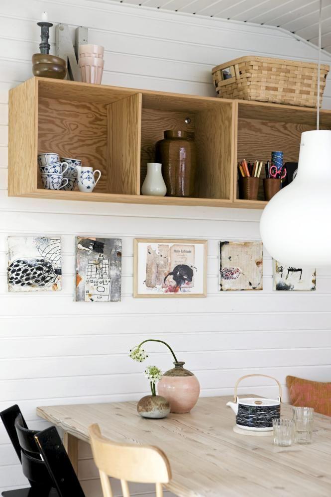 Beboerne har plassert en trehylle på veggen over spisebordet, og fylt den med både pyntegjenstander og bruksgjenstander. Den er derfor både dekorativ og praktisk.