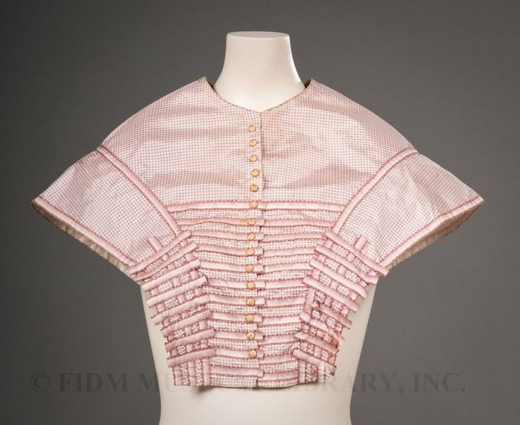 """""""Pelerine, ca. 1855-1860. Pelerines created a smooth, sloped shoulder-line, a desirable silhouette throughout much of the 19th century. Usually cut with a high-neck, pelerines were often made of the same fabric as the dress worn underneath. Trimmings usually consisted of coordinating ribbon, self-fabric bias or simple piping."""""""