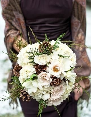 A bridesmaid in a dark eggplant dress and shawl with a pine cone and flower bouquet.